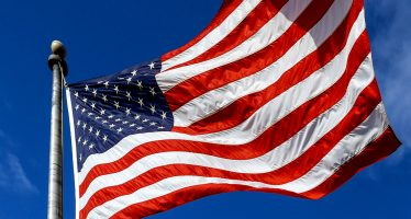 USA. Wind blown flag of the United States of America over sky background.